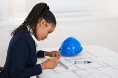Young African Businesswoman Drawing Blueprint At Office Desk Stock Photos
