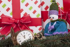Christmas card, fir branches, snowman and gold watch - stock photo