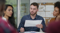 4K Young casual business group looking at paperwork & discussing ideas - stock footage