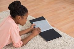 Young African Woman Looking Blank Photo Album In Living Room Stock Photos
