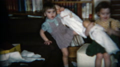 Stock Video Footage of 1960: Girls showing off their large baby dolls inside the cozy house.