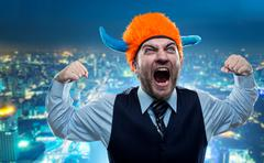 Businessman in party helmet shouting - stock photo