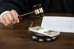 Midsection of corrupt judge hitting dollar bundle on gavel at desk in courtro - stock photo