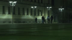 People walking at night under street lamps Square Stock Footage