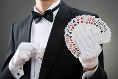 Midsection of magician showing fanned out cards against gray background Stock Photos