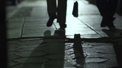 Silhouettes of walking legs  under street lamp in slow motion Stock Footage