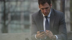 4K Serious businessman using mobile phone outdoors in the city.  - stock footage
