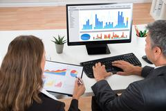 Two Businesspeople Analyzing Graphs At Desk In Office Stock Photos