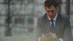 4K Smiling businessman using mobile phone outdoors in the city.  Stock Footage