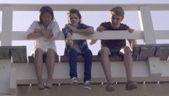 Multiethnic Teens Sit On A Bridge, Girl Points To Something Below, Friends Look Stock Footage