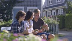 Multiethnic Teens Eat Cookies And Chat On New England Town Bench Stock Footage