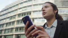 4K Attractive businesswoman using smartphone for navigation outdoors in the city Stock Footage