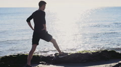 Male runner warming up un the sun light on the beach slow motion Stock Footage
