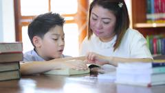 Reading with teacher - an elementary school boy reads aloud to her teacher Stock Footage