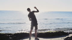 male runner warming up un the sun light on the beach slow motion - stock footage