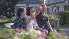 Teens Sit On Town Bench, And Eat Giant Cookies, They Cheers With The Cookies - stock footage