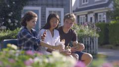 Multiethnic Teens Sit On Bench, Girl Takes Photo Of Cookie, Her Friends Eat Stock Footage
