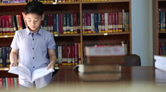 Little asian boy bee bored with reading,library in thailand Stock Footage