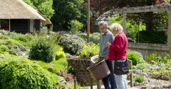 Gardener and woman talk botanic garden Stock Footage