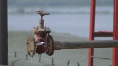 Big old faucet flows slow motion Stock Footage