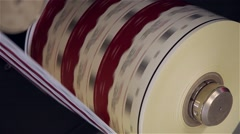 Roll of paper being printed in a printing press, pan shot Stock Footage
