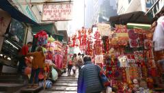 POV walk uphill along marketplace alley, many stalls with bright decorations Stock Footage