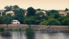 Van Passes Houses By River In Developing Country Stock Footage