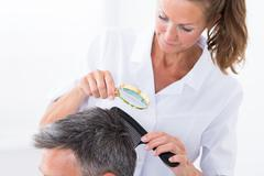 Female Dermatologist Looking At Patient's Hair Through Magnifying Glass - stock photo