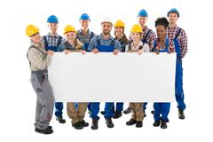 Portrait of happy construction workers holding blank billboard against white  Stock Photos