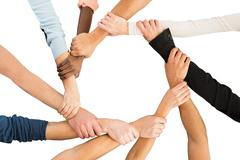 Directly above shot of people holding each other's hand in showing unity agai Stock Photos