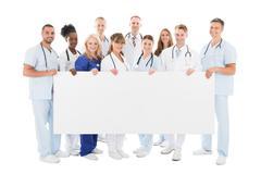 Full length portrait of confident multiethnic medical team holding blank bill Stock Photos
