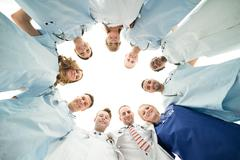 Directly below portrait of confident medical team standing in huddle against  - stock photo