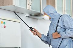Side view of exterminator in workwear spraying pesticide in kitchen. Pest con - stock photo