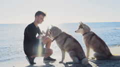 young male training his dogs on the beach slow motion - stock footage