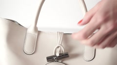 Girl with red nail polish opening and closing her beige leather bag Stock Footage