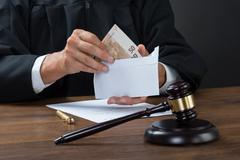 Stock Photo of Midsection of judge removing money from envelope in courtroom