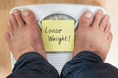 Low section of man standing on scale with loose weight sign Stock Photos