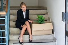 Full length of sad businesswoman with belongings sitting on steps at office - stock photo