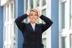 Sad young businesswoman with hands on head standing against buildings - stock photo