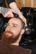 Cheerful hipster is attending a hairdressing saloon - stock photo