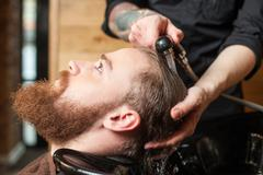 Professional male hairdresser is cleaning human head - stock photo