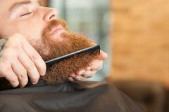 Skillful male hairstylist is working with comb Stock Photos
