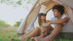 Stock Video Footage of The girl and the guy of different races have a rest in tent and stir