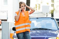 Young woman in reflective jacket using mobile phone with broken down car on s - stock photo