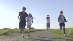 Multiethnic Group Of Friends Run Away From Beautiful Lighthouse, Toward Camera Stock Footage