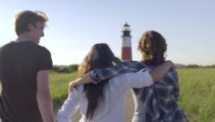 Multiethnic Group Of Excited Friends Walk Toward Historic Lighthouse Stock Footage