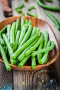 Pods of fresh organic green beans in a wooden bowl closeup Stock Photos