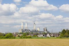A decommissioned lignite power station behind a village - stock photo
