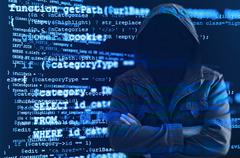 Hacker without face surrounded by source code Stock Photos