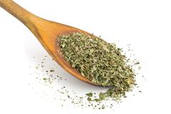 Dried oregano on wooden spoon - stock photo